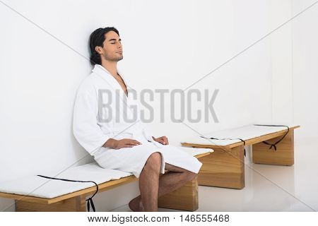 Relaxed young man is enjoying solitude in restroom at wellness center. He is sitting on bench in bathrobe with relaxation
