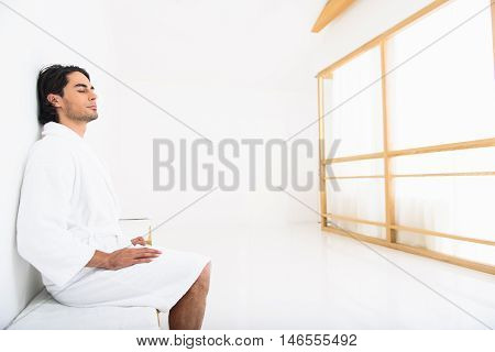 Young man is napping after procedure at spa. He is sitting in bathrobe and leaning back on wall