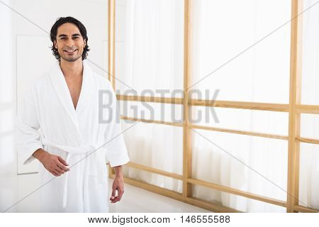 Good morning. Happy young man is standing in bathrobe at home. He is looking at camera and smiling