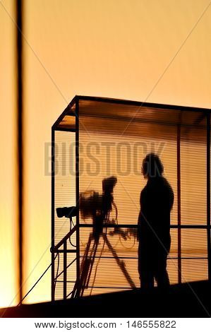 Cameraman's silhouette broadcasting live from a stadium