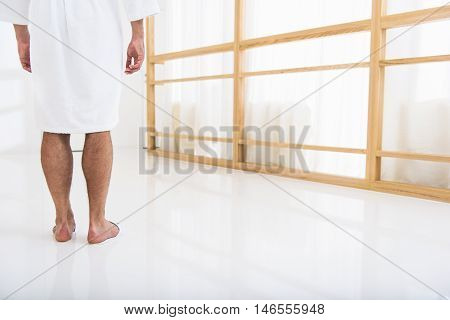 Close up of male legs standing on white flooring near window in restroom. Man is wearing bathrobe. Focus on his back