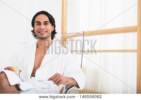 This is the best vacation. Carefree young man is relaxing on confortable chair and drinking lemonade. He is looking at camera and laughing. Man is wearing white bathrobe