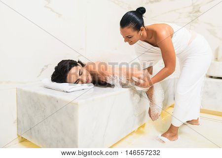 Skillful masseuse is massaging male body and smiling. Young man is lying on bench in sauna covered with foam. His eyes are closed with pleasure