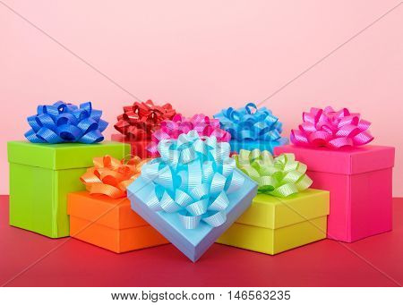 rows of bright colorful party boxes with shiny bows on top magenta table top pink background. Copy space