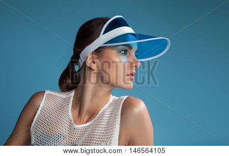brunette fashion model with bright makeup on studio blue background