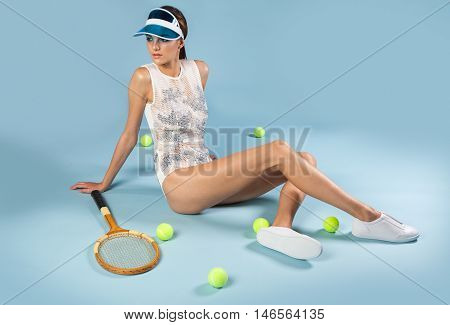 sexy brunette woman sitting on floor near tennis racquet and balls on blue background
