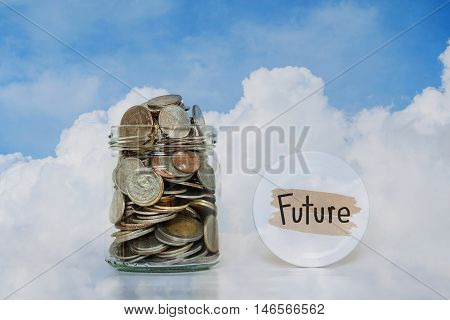 Coins in glass jar - saving money for Future, on blue sky and white clouds