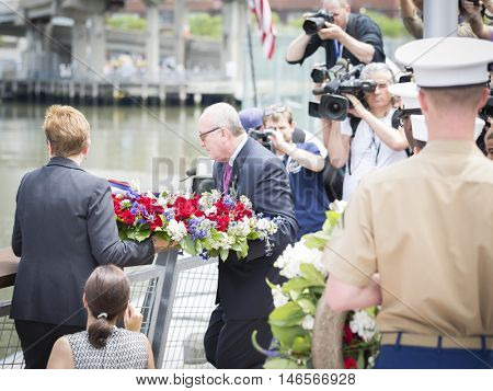 NEW YORK MAY 30 2016: US veterans toss a ceremonial wreath of flowers into the water at the Memorial Day Observance service on the Intrepid Sea, Air & Space Museum during Fleet Week NY 2016.