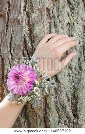 Purple and grey wrist corsage on a hand