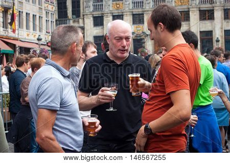 BELGIUM, BRUSSELS - SEPTEMBER 07, 2014: Belgian Beer Weekend 2014. The most famous beer festival in Belgium. Mans with a glasses of beer at the festival.