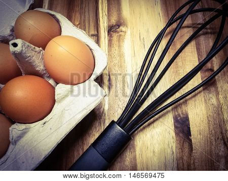 brown organic eggs and a whisk on a wood surface