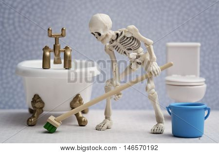 A skeleton cleaning bathroom floor with a brush
