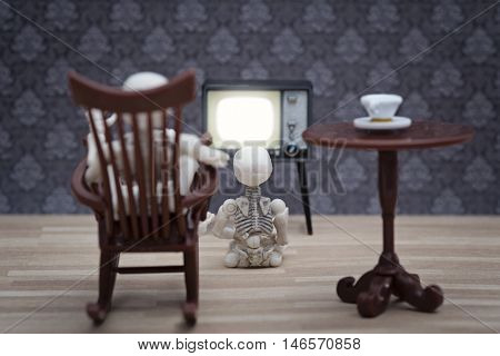 A skeleton in a rocking chair and little skeleton sitting and watching TV