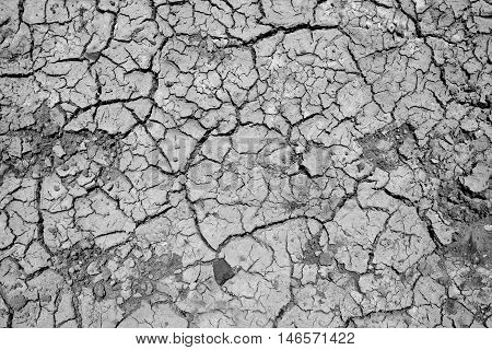 Texture of land dried up by drought, the ground cracks background with grunge and vignette tone