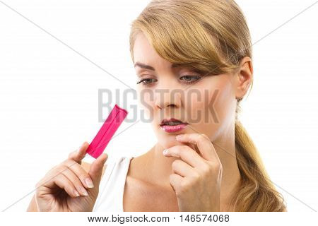 Unhappy And Worried Woman Looking At Pregnancy Test With Positive Result