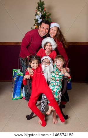 A family sits on the lap of a young bearded Santa Claus for a Christmas portrait. Everyone is wearing Christmas themed pajamas.