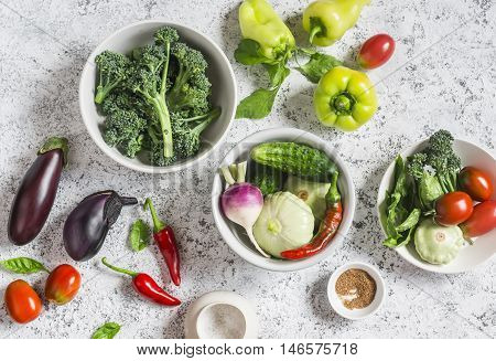 Fresh vegetables - broccoli peppers tomatoes eggplant squash turnips on a light background top view