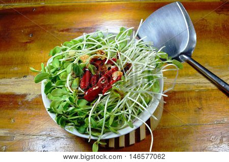 raw sunflower sprout and iron flipper prepare to cook
