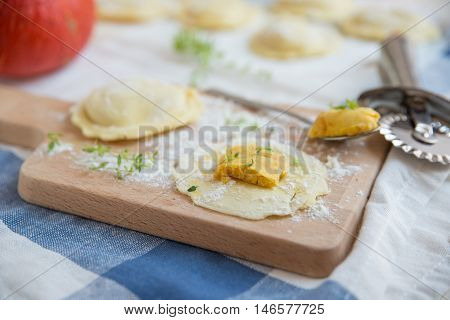 homemade stuffed with pumpkin ravioli on a wooden board