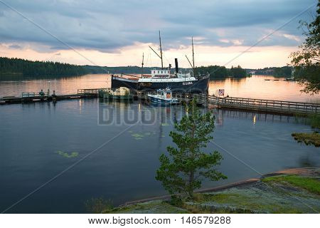 SAVONLINNA, FINLAND - AUGUST 20, 2016: View of the marina museum of ancient ships in the august twilight. Tourist landmark of the city Savonlinna