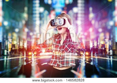 Double exposure, Young girl getting experience VR headset, is using augmented reality eyeglasses, being in a virtual reality. In city at night
