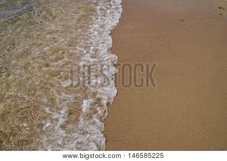 Waves lapping on the sandy shore. Sea beach.