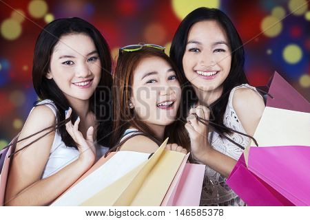 Lovely young shoppers smiling at the camera while carrying shopping bags with bokeh background