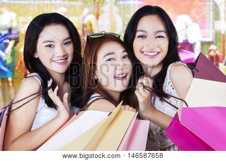 Pretty shoppers smiling at the camera while carrying shopping bags in the shopping center