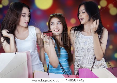 Teenage shoppers using a credit card for shopping while carrying shopping bags with defocused background