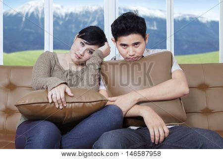 Two young Asian bored couple sitting on the couch with pillow at home