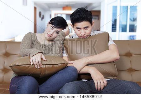 Two young Asian couple sitting on the couch while looking at the camera and looks bored