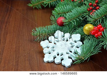 Wooden painted handmade snowflake - New Year holiday attributes. preparing for midnight. Branches of a Christmas tree red berries balls wooden toys. Colorful Christmas decorations.
