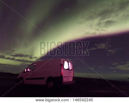 A Breathtaking View of Dancing Northern Lights on the Winter Night sky over our White Camper Van, Iceland