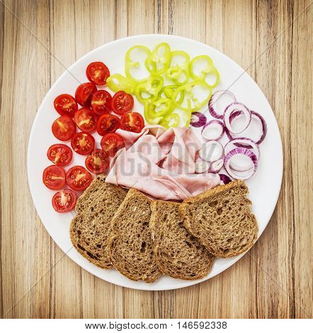 Tasty whole wheat bread with butter ham onion paprika and cherry tomatoes. Food theme. Refreshments for guests. One full portion.