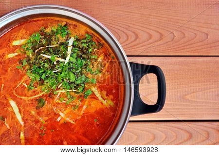 Full pot of red soup with parsley top view