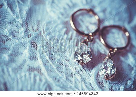 Fine jewelry: earrings on the white wedding dress
