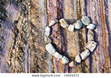 Stone heart on colourful rock background