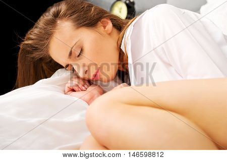 Woman on bed with painfull stomach pain.