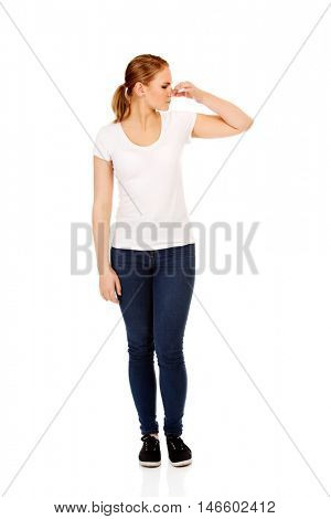 Young woman holding her nose because of a bad smell