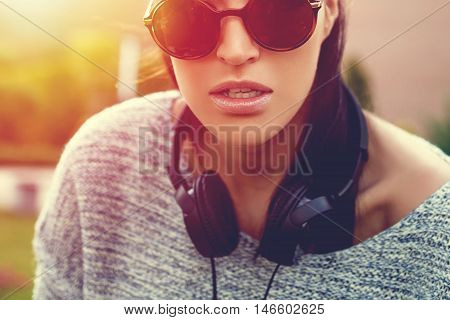 Woman DJ in sunset with headphones on neck closeup