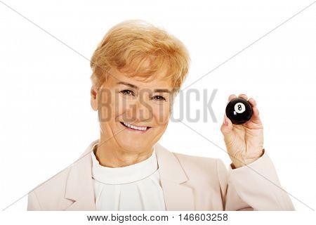 Happy elderly business woman holding eight billard-ball