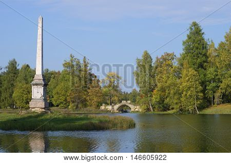 GATCHINA, RUSSIA - SEPTEMBER 24, 2015: View on the Chesme obelisk and the Humpback bridge, september day. Historical landmark of the city Gatchina