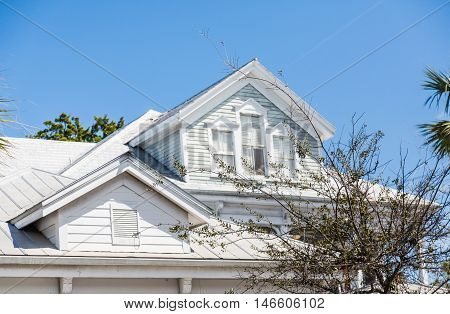 Dormers on Old White Wood Home under blue sky