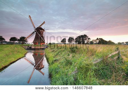 charming Dutch windmill by river at sunrise Groningen Netherlands
