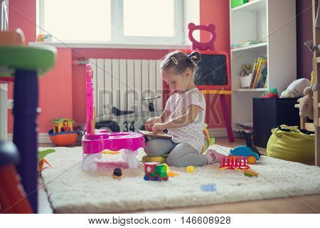 Little Girl Playing With Toys In The Children Room