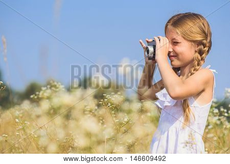 Joyful girl is taking photos by camera in meadow. She is standing among daisies and smiling