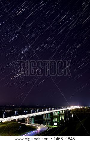 Scenic view with the bridge over the river and the stars in the form of tracks in the night sky shot on a long exposure