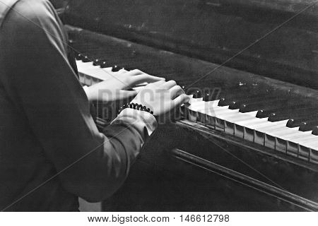 female hands on a piano in black and white retro style.