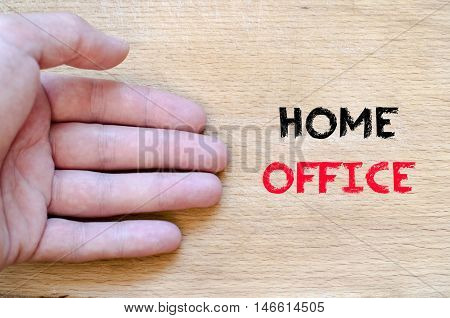 Human hand over wooden background and home office text concept