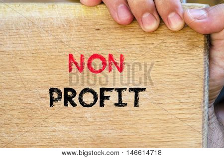 Human hand over wooden background and non profit text concept